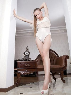 Milena D looks quite sophisticated posing on her leather chair.  Wearing a stunning cream lace bodysuit, with  matching cream colored platform stilett